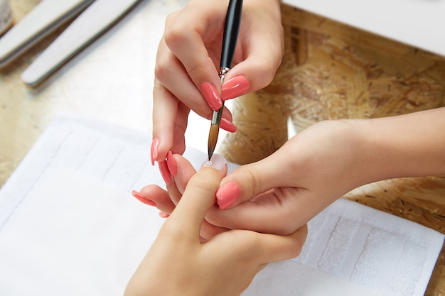 Nails painting woman with brush in nail salon