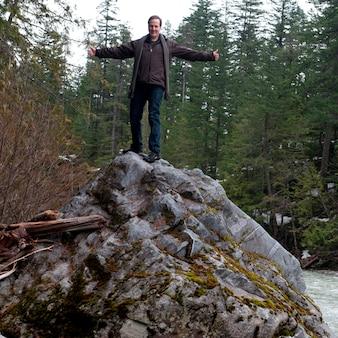 川沿いの岩の上に腕を伸ばして立っている男、nairn falls provincial park、ウィスラー、ブリティッシュ・コロンビア、カナダ