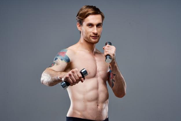 タトゥーとダンベルを手に持った裸のアスリート電話フィットネスボディービル