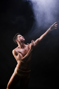 Naked athletic man standing and raising hands near smoke
