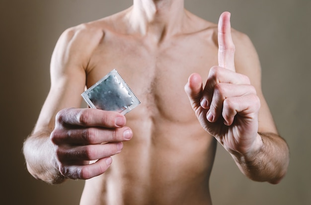 Naked, attractive man in black jeans is holding a condom in his waist, and the other hand is pointing up with a finger