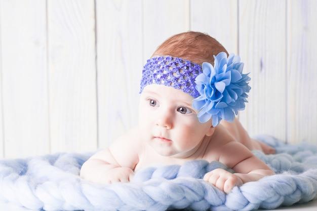 그녀의 머리 주위에 보라색 머리띠와 부드러운 커튼에 누워 벌거 벗은 아기 소녀