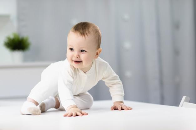 明るい部屋に座っている白いスーツで裸の赤ちゃん