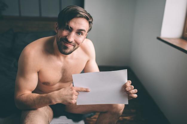 裸のひげを生やした黒髪のハンサムな男がベッドの上に紙の空のシートを保持しています。ホームインテリア。