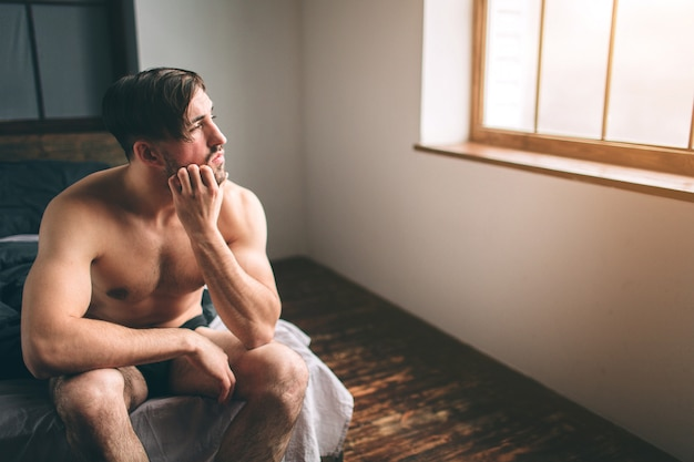 Naked bearded dark-hair thoughtful man sitting in bed