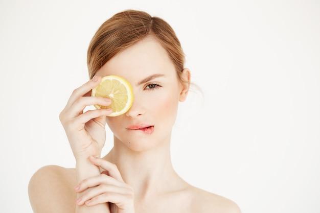 Голая красивая девушка с чистой здоровой кожей, кусая губы, скрывая глаз за ломтиком лимона. салон спа-косметологии.