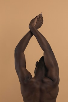 Naked black person with hands in the air from behind shot