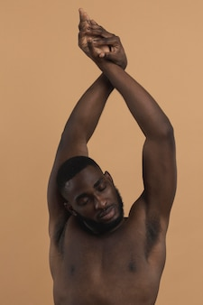 Naked black person with hands in the air