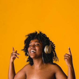 Naked black young female singing in headset in studio
