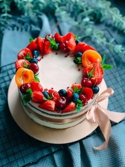 딸기로 장식 된 크림이 든 벌거 벗은 케이크. 프리미엄 사진