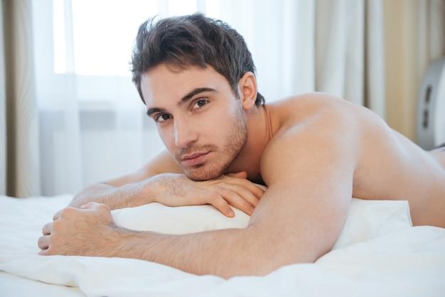 Голый спокойный мужчина, лежащий на кровати. вид сбоку