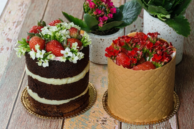 Naked chocolate cake next to dress cake covered with textured board. decorated with strawberries and kalanchoe flowers.