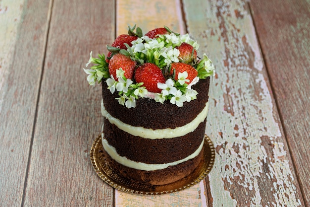 Naked chocolate cake, filled with coconut brigadeiro. decorated with strawberries and white kalanchoe flowers (on the table).