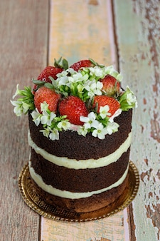Naked chocolate cake, filled with coconut brigadeiro. decorated with strawberries and white kalanchoe flowers (vertical photo).
