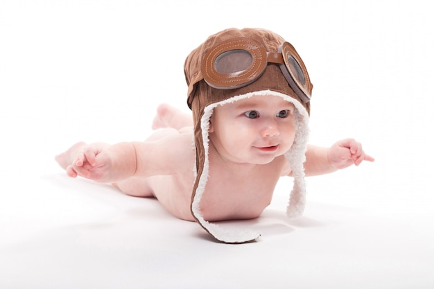 Naked cute smiling baby in the cap of the pilot is flying on a w