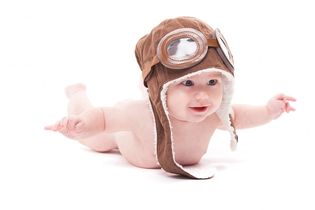 Naked cute smiling baby in the cap of the pilot is flying  a w