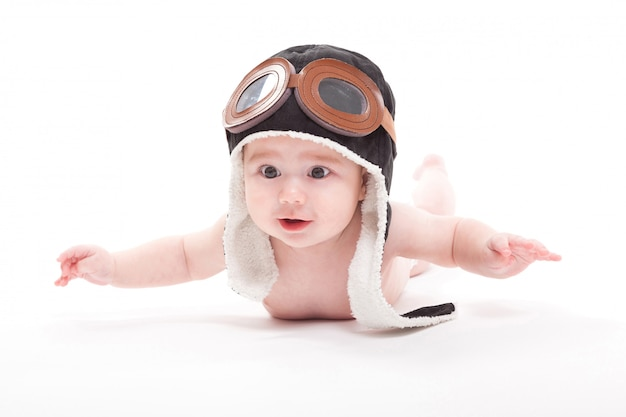 Naked cute smiling baby in the cap of the pilot is flying