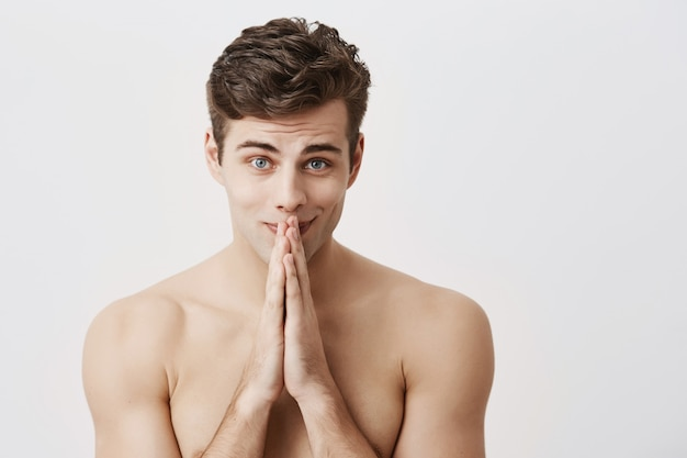 Naked gently smiling caucasian male model with trendy haircut and healthy pure skin keeps palms together, has good mood, posing . beauty and youth concept.