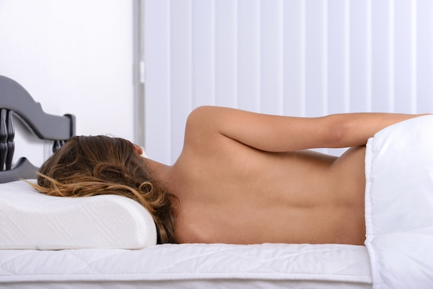 Naked girl on the bed in bed at home.