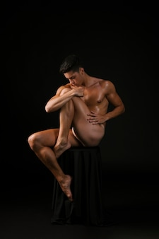 Naked guy embracing knee