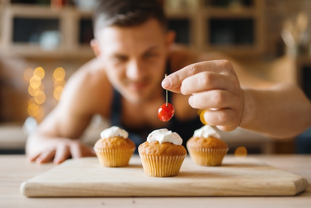 Naked man in apron cooking dessert with cherry on the kitchen. nude male person preparing breakfast at home, food preparation without clothes