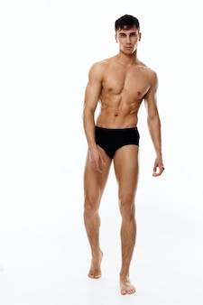 Naked man athlete in full growth on a light background black panties model