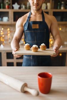 앞치마에 벌거 벗은 남자는 부엌에 달콤한 디저트와 함께 트레이를 보유하고 있습니다. 집에서 아침 식사를 준비하는 누드 남성 사람, 옷없이 음식 준비