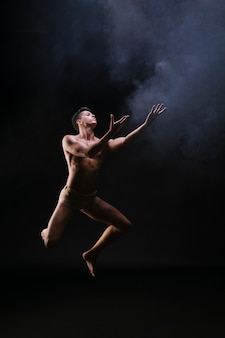 Naked man jumping and raising hands against black background