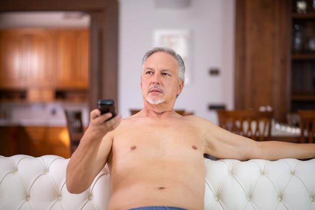 Голый мужчина расслабляется и смотрит телевизор дома