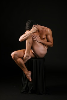 Naked man siting covering face with hands