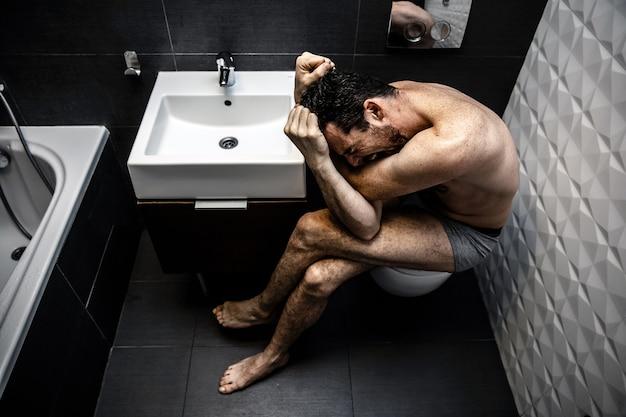 오래 된 도시 화장실에 앉아 벌거 벗은 남자. 사람은 끔찍한 정서적 고통과 무력감을 느낍니다. 중독자는 기분이 나쁘다