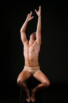 Naked man stretching up with both hands