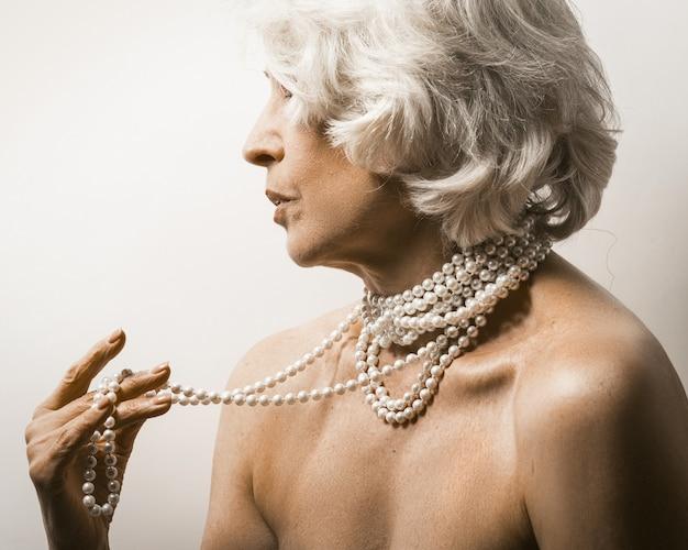 白の裸の成熟した女性。彼女の首にパールビーズと白い背景の上の裸の肩を示す成熟した女性の縦断ビュー。