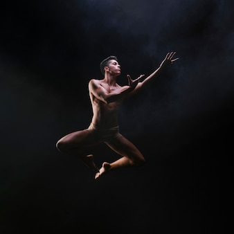Naked muscled male jumping and raising hands