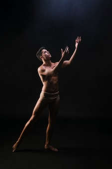 Naked muscled male standing and raising hands