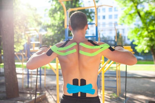 Голый мускулистый мужчина тренируется с фитнес-веревкой на спортивной площадке. вид сзади молодого неузнаваемого культуриста с эластичной кинезиологической тейпом на бодибилдинге на открытом воздухе. концепция реабилитации.