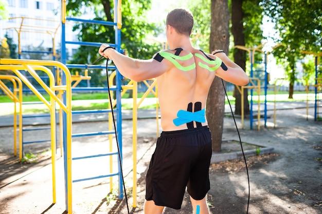 スポーツグラウンドでフィットネスロープを使ってトレーニングしている裸の筋肉の男
