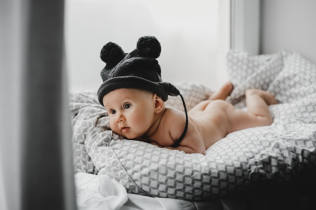 Naked newborn boy in a warm winter hat lies on the soft blanket before a bright window
