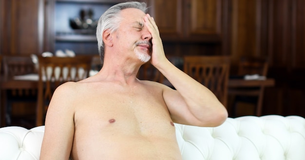 Naked senior man suffering for hot weather while sitting on his sofa