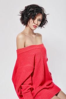 짧은 머리를 가진 벌거 벗은 섹시한 여자. 흰색 바탕에 빨간 스웨터를 입고 포즈를 취하는 소녀. 완벽한 깨끗한 피부, 갈색 머리 여자의 섹시한 누드 바디. 피부 재생 및 수분 공급