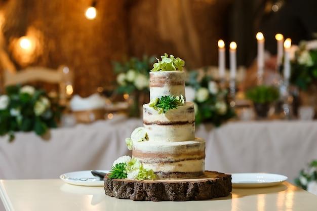 結婚披露宴で新鮮な花の緑のおいしいデザートで飾られた裸のウエディングケーキ