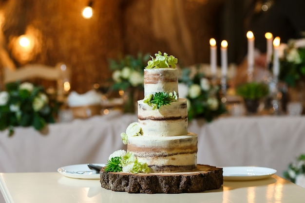 Naked wedding cake decorated with fresh flowers greenery delicious dessert at wedding banquet