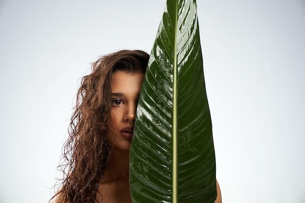 큰 녹색 잎 뒤에 얼굴을 숨기고 벌 거 벗은 여자