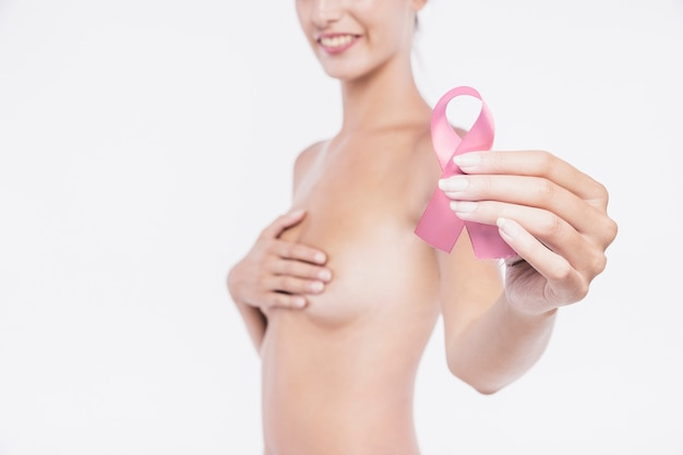 Naked woman holding pink awareness ribbon