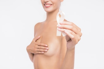 Naked woman holding white awareness ribbon