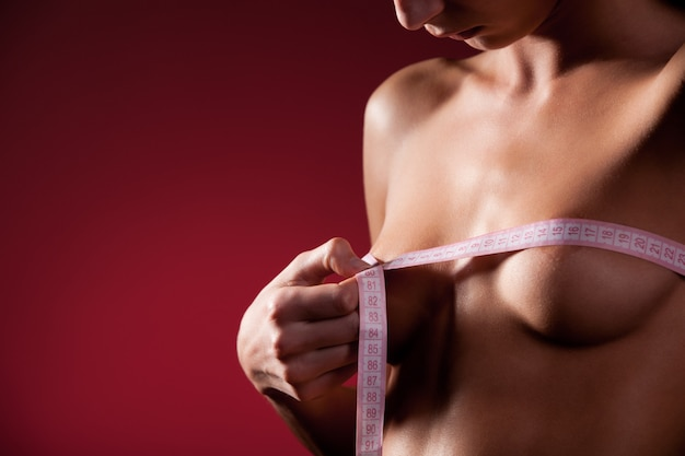 Naked woman measures breasts with measuring tape