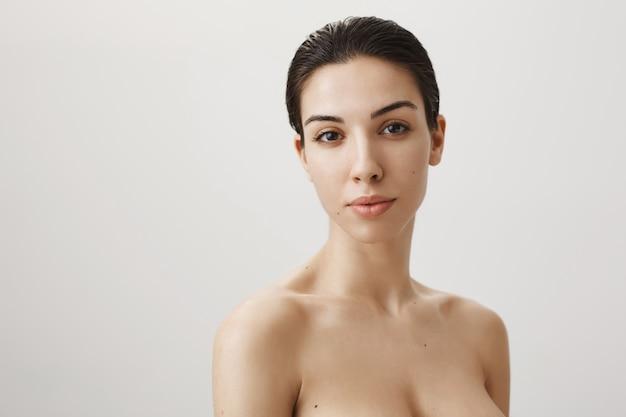 灰色の上に立って、正面を見て裸の女性