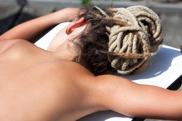 Naked woman sunbathing on sunbed