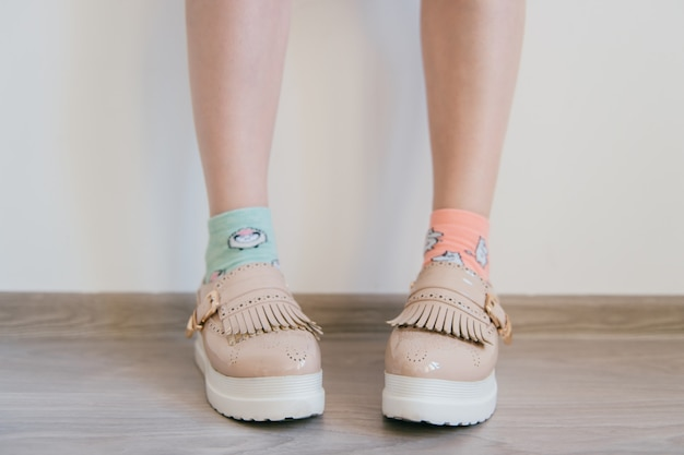 Naked women`s feet in feminine business bright leather shoes with tankette and white sole standing at home. female feet in mismatched cotton colorful socks. innocence and youth lifestyle.