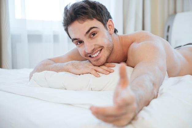 Обнаженный молодой человек, лежащий на кровати. вид сбоку
